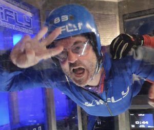 male facing camera, laid out horizontally (because in a wind tunnel). Open-mouthed, blue helmet, goggles