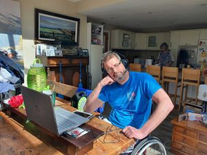 Left, a long table with a laptop. Leaning against the table, a male wheelchair user wearing a blue T-shirt, speaker headphones. A kitchen in the background