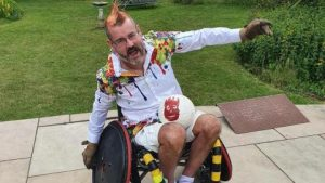 A very handsome man (actually a 53 year-old with a dodgy orange Mohican} sits happily in his Wheelchair rugby Chair. His arms are spread airplane wide and he has a volleybally in his lap.